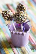 Stock Photo of Pail with three cake pops on colourful ground