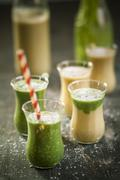 Glasses of spinach smoothie and mango smoothie with desiccated coconut on wooden - stock photo