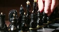 Chess black figures-game start (hand touching a pawn and then the officer) Stock Footage