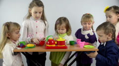 A group of children simulates cooking in a bright toy ware Stock Footage