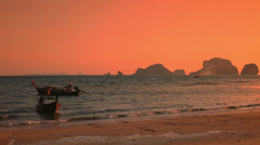 Yellow sunset on ocean coast of Thailand. Boats on evening sea waves and cliffs Stock Footage