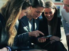 Happy group of business people watching something on smartphone NTSC - stock footage