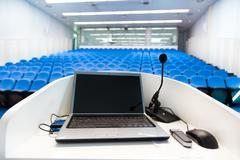 Laptop on the rostrum in conference hall. Stock Photos