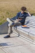 Germany, Baden/Wurttemberg, Teenage boy sitting on bench, learning - stock photo
