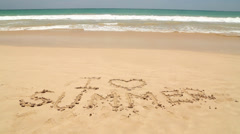 Girl walking in front of words I love summer written in sand on beach Stock Footage