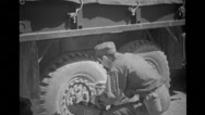 Military soldier with Geiger Counter checking truck wheel for radiation Stock Footage