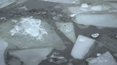 Ice chunks floating by in water close up - stock footage