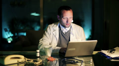 Young doctor working on laptop computer late at night HD - stock footage