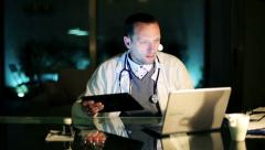 Young doctor working on laptop and tablet computer late at night HD Stock Footage