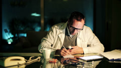 Doctor writing rx prescription at office late at night HD Stock Footage