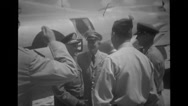 Military officers shaking hands with each other beside military aeroplane Stock Footage