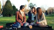Stock Video Footage of Three young girlfriends talking on cellphone relaxing on blanket in park HD