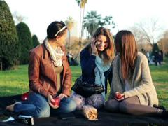 Stock Video Footage of Three young girlfriends talking on cellphone relaxing on blanket in park NTSC