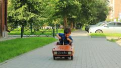 Three year old boy riding a toy car Stock Footage
