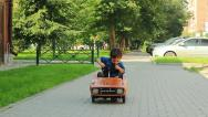 Stock Video Footage of Three year old boy riding a toy car