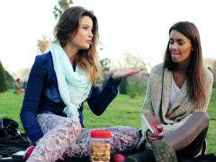 Two girlfriends fight, argue while sitting on grass in the park NTSC Stock Footage