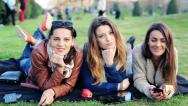 Stock Video Footage of Happy girlfriends relaxing on blanket in the park HD