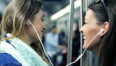 Stock Video Footage of Happy girlfriends listen to music and singing while ride metro train HD