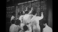 Men writing on blackboard in stock market Stock Footage