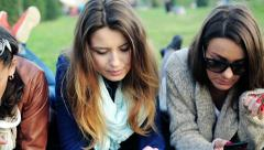 Girlfriends with tablet and smartphone relaxing lying on the grass in park HD Stock Footage