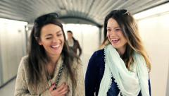 Happy girlfriends chatting while walking in metro tunel HD Stock Footage