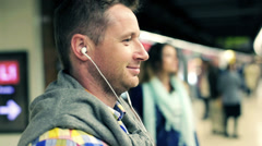 Happy young man listen to the music on metro station HD - stock footage