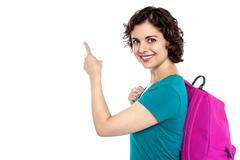 Pretty student indicating towards copy space area - stock photo