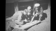 Navy Chief watching two army sergeants soldering on board beside building Stock Footage