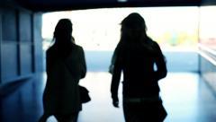 Silhouette of two women walking in tunel HD Stock Footage