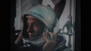 Astronaut wearing helmet and technicians adjusting Stock Footage
