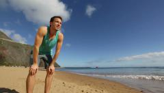 Sport man running on beach stopping sweating Stock Footage