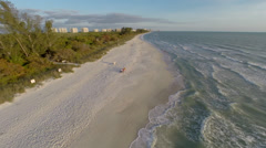Cruising low over the white sand beach along the Gulf of Mexico Stock Footage