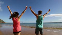 Happy couple cheering raising arms celebrating Stock Footage