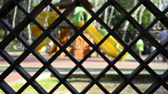 Children play game at park, playground behind of wood lattice, mesh Stock Footage