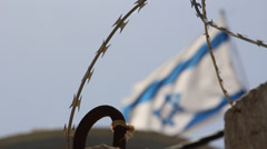 Israeli flag flying on the border with barbed wire - stock footage
