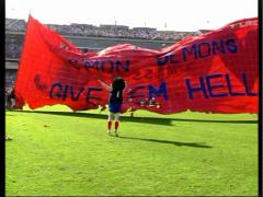 Stock Video Footage of Melbourne Football, demons run through sign