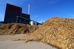 Stock Photo of bio power plant with storage of wooden fuel against blue sky