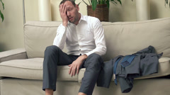 Tired businessman having headache on sofa at home, super slow motion HD - stock footage