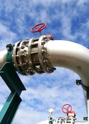 industrial pipelines and valve with a natural blue background - stock photo