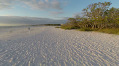 Gliding along a white sand beach at sunset then lifting up over the inlet Stock Footage