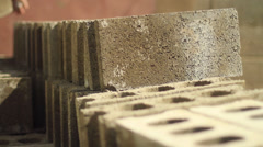 Laying construction blocks into a pile - 2 clips Stock Footage