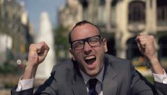 Stock Video Footage of Crazy, successful excited businessman screaming to camera in city HD