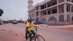 Ghana mosque with Cyclists Stock Footage