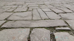 Dolly: Ancient cobblestone pavement in old town - stock footage