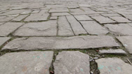 Dolly: Ancient cobblestone pavement in old town Stock Footage