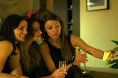 Cheerful girlfriends taking photo with cellphone during party NTSC - stock footage