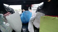 Woman unloads groceries in plastic and paper bags into the trunk of her car Stock Footage