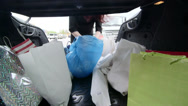 Stock Video Footage of Woman unloads groceries in plastic and paper bags into the trunk of her car
