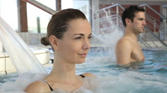 Woman enjoying hydrojet shower in spa pool Stock Footage
