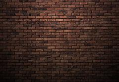 dimly lit old brick wall - stock photo